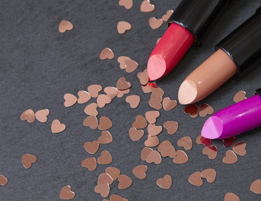 Lipstick make up with love heart shaped confetti scattered on a dark slate background forming a page border
